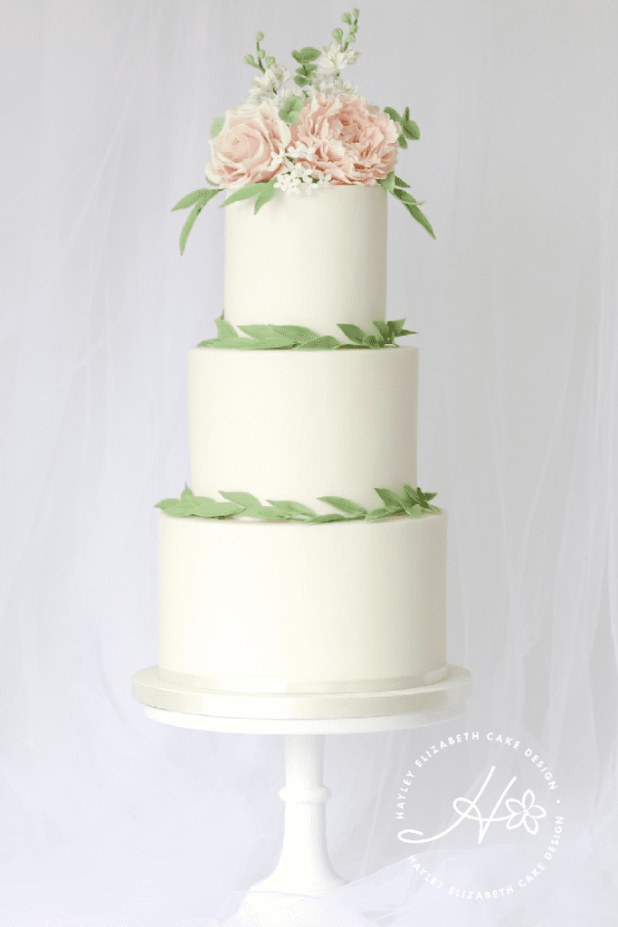 Luxury wedding cake from Hayley Elizabeth Cake Design, sugar flower peonies, foliage, sugar roses. Fondant icing, textured wedding cake, dessert table, wedding cake inspiration, elegant wedding cakes, olive leaf wedding cake, Mediterranean wedding cake, peach and cream wedding cake, destination wedding