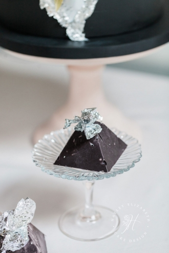Black chocolate pyramid on wedding cake table | chocolate sweet treats on wedding cake table | Discover more edible wedding favor ideas for guests | wedding favor ideas | edible wedding favors | wedding favours chocolate | chocolate pyramids wedding | black wedding cake | modern wedding theme | contemporary wedding | chic wedding theme | london wedding cake table | elegant wedding cake table | dessert table styling | dessert table ideas #weddingfavours #modernwedding #weddingcakes
