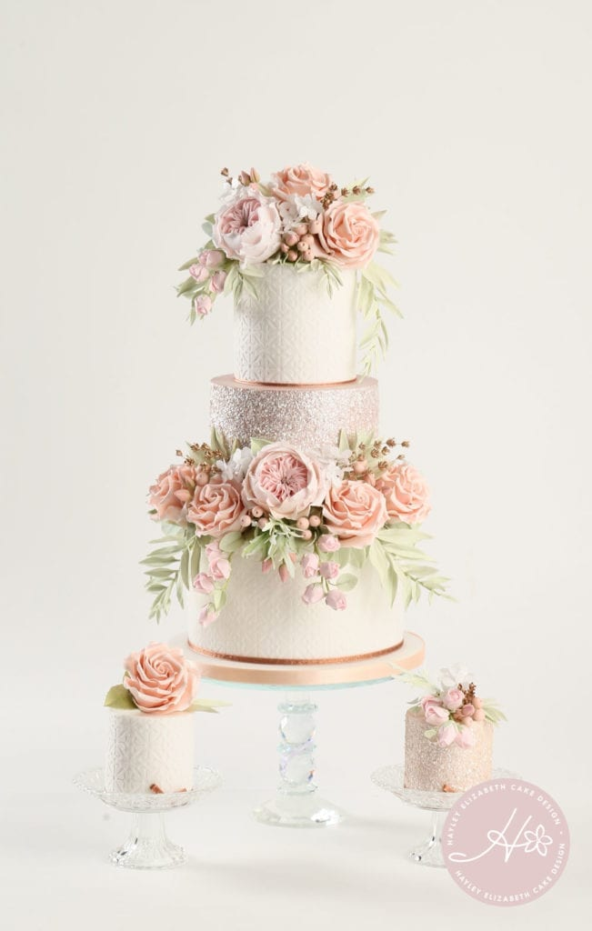 Luxury wedding cake from Hayley Elizabeth Cake Design, sugar flower peonies, foliage, sugar roses and rose gold shimmer. Fondant icing, textured wedding cake, dessert table, wedding cake inspiration, elegant wedding cakes, Hampshire cake designer.