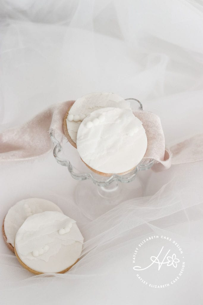 White iced biscuits, dessert table, wedding favours, edible wedding favours, pretty sweet treats, wedding sweet table, wedding cake table, pretty desserts, christening favours, fine art dessert table, luxury party favours, bridal shower treats