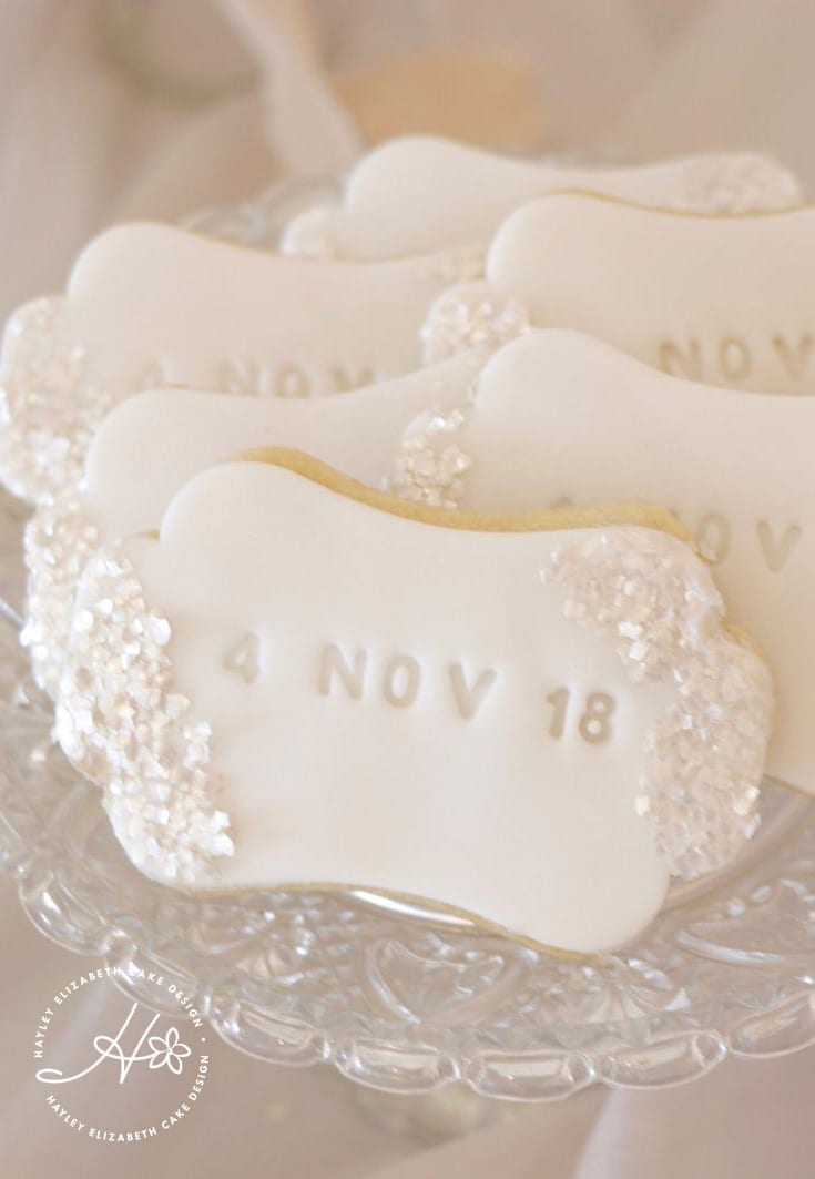 White and silver dessert table, luxury wedding cake, cake pops, iced biscuits, mini cakes, silver and white wedding cake, dessert bar, white sequin wedding cake, sugar flowers, wedding cake inspiration