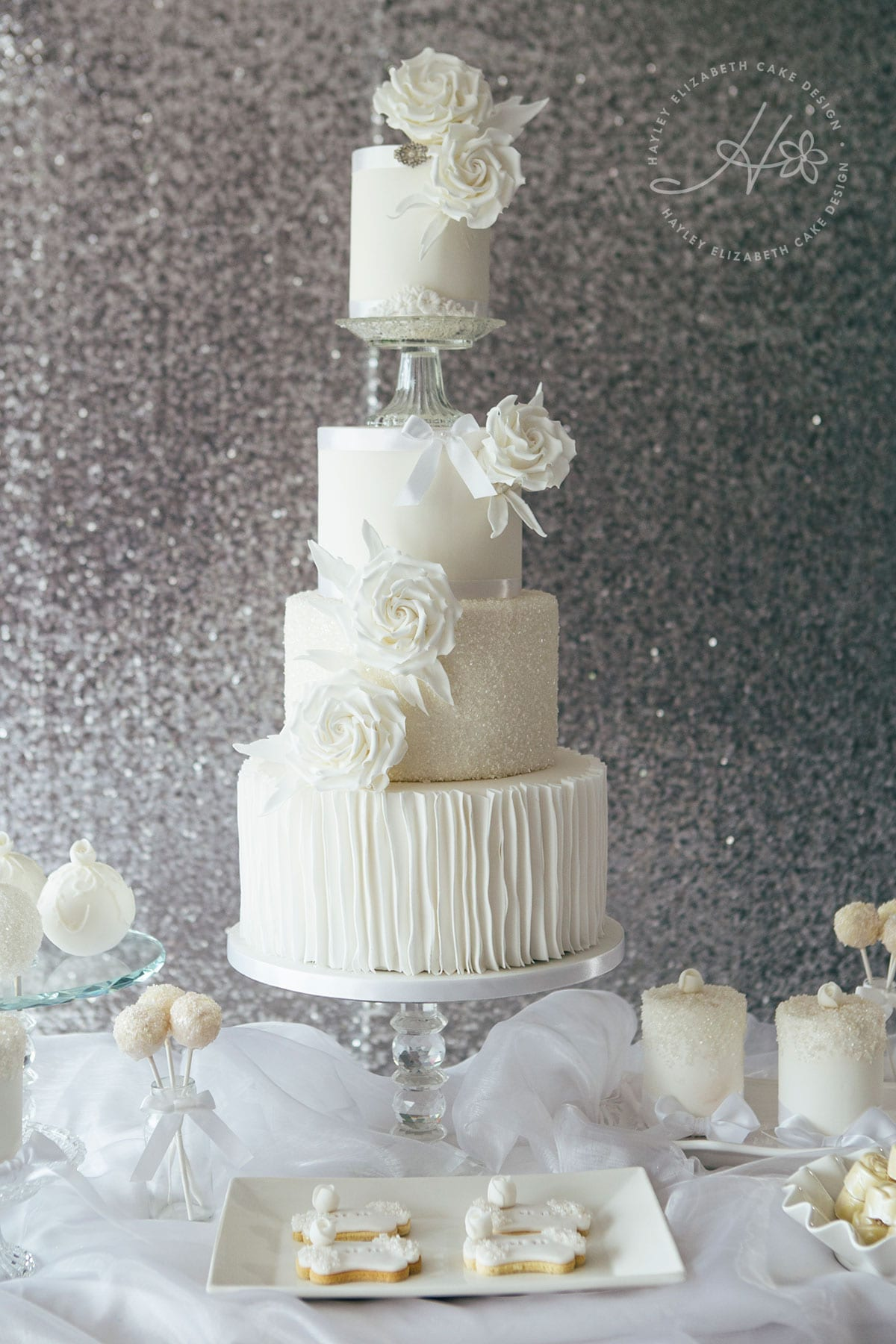 All white dessert table, luxury wedding cake, cake pops, iced biscuits, mini cakes, silver and white wedding cake, dessert bar, white sequin wedding cake, sugar flowers, wedding cake inspiration