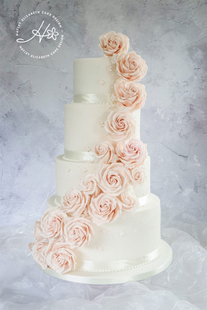 Luxury wedding cake from Hayley Elizabeth Cake Design, Dorset and Hampshire cake designer. White and blush wedding cake, sugar flowers, pink roses, rose cascade cake, white and pink wedding cake, blush sugar roses, white wedding cake, elegant wedding cake, wedding cake ideas.