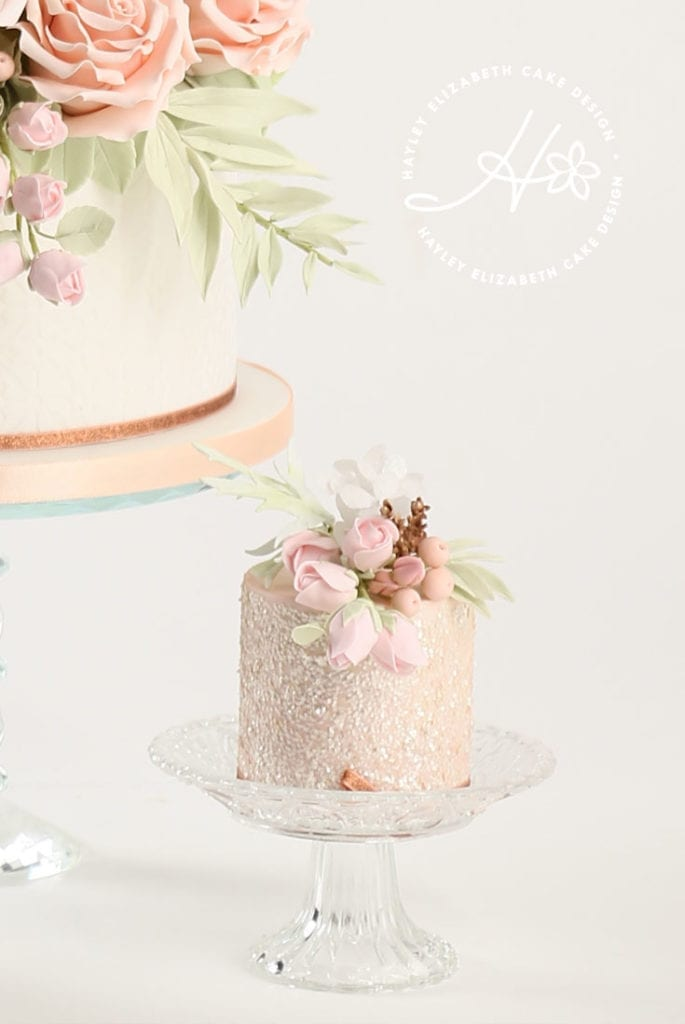Luxury wedding cake from Hayley Elizabeth Cake Design, sugar flower peonies, foliage, sugar roses and rose gold shimmer. Fondant icing, textured wedding cake, dessert table, wedding cake inspiration, elegant wedding cakes, Hampshire cake designer., blush and rose gold wedding cake