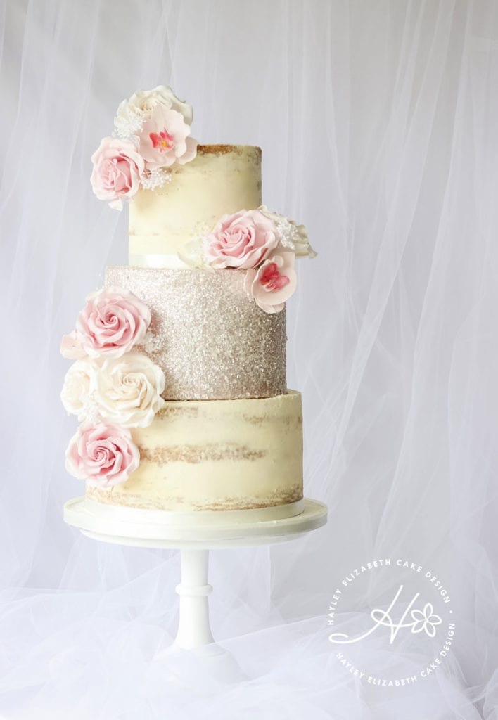 Semi naked buttercream cake with sequins and sugar flowers, from Hayley Elizabeth, Cake Designer. White wedding cake, ruffle wedding cake, luxury wedding cake, elegant wedding cake, wedding cake inspiration, sequin wedding cake, spring wedding cake