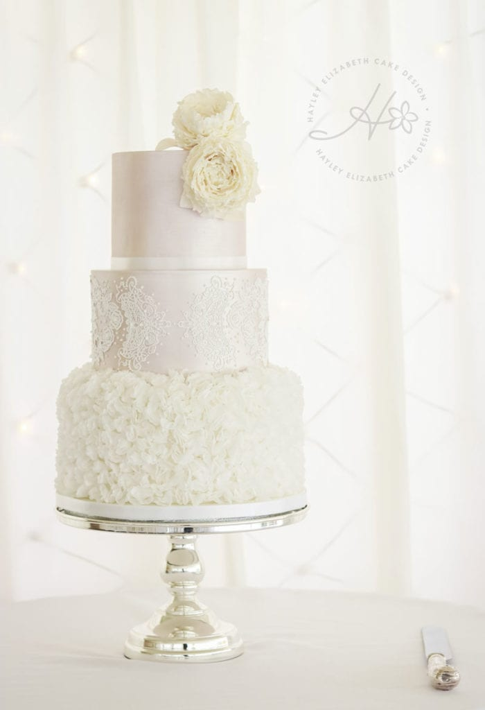 Blush and white wedding cake from Hayley Elizabeth, Cake Designer. White wedding cake, ruffle wedding cake, luxury wedding cake, elegant wedding cake, wedding cake inspiration, blush shimmer wedding cake, lace wedding cake, winter wedding cake