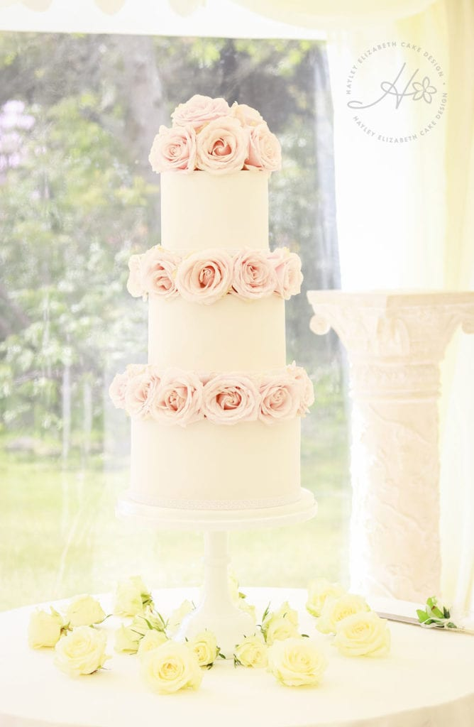 White wedding cake with pink roses. Luxury wedding cake, wedding cake inspiration, fondant icing, elegant wedding cake, pink and white wedding cake, Hayley Elizabeth cake design Hampshire and Dorset.