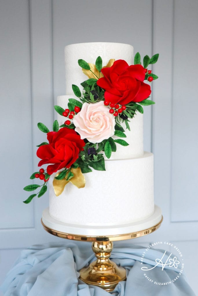 Red green and gold wedding cake, luxury wedding cakes, elegant wedding cakes, christmas wedding cakes, red sugar flowers, holly sugar flowers, festive wedding cake, winter wedding cakes, wedding cake ideas, wedding cake inspiration, Hampshire wedding venues