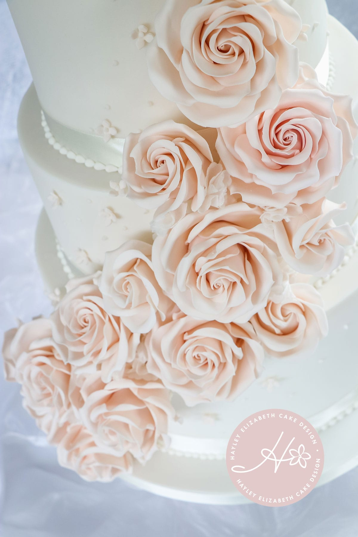 Blush sugar flowers, luxury wedding cake from Hayley Elizabeth Cake Design, Dorset and Hampshire cake designer. White and blush wedding cake, sugar flowers, pink roses, rose cascade cake, white and pink wedding cake, blush sugar roses, white wedding cake, elegant wedding cake, wedding cake ideas.