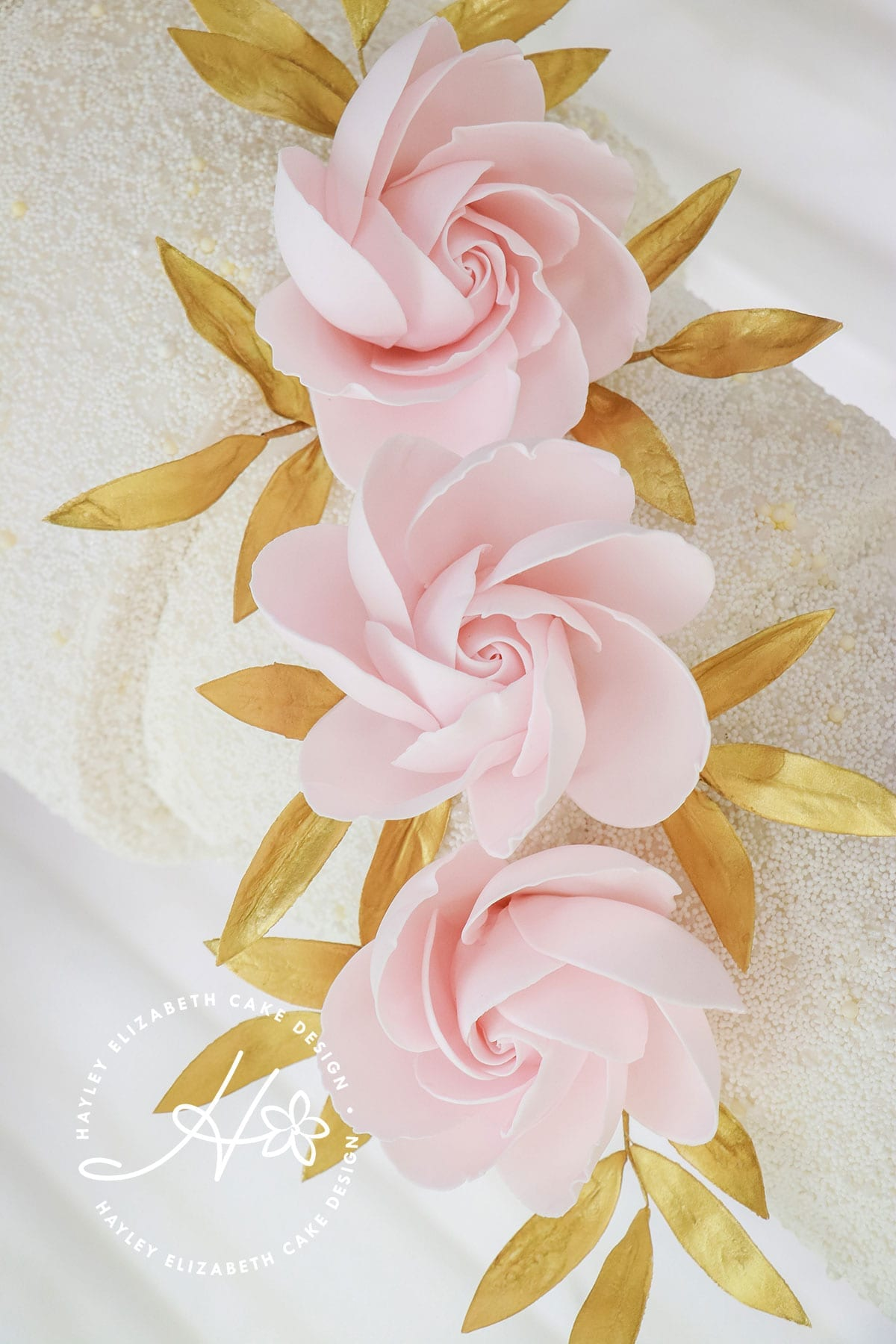 Textured wedding cake with contemporary roses and gold leaves. White, gold and pink wedding cake, elegant wedding cake, sugar flowers, Hampshire and Dorset cake design, wedding cake inspiration