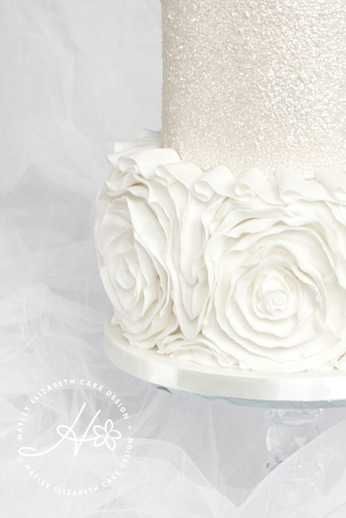 All white wedding cake from Hayley Elizabeth, Cake Designer . White wedding cake, ruffle wedding cake, luxury wedding cake, elegant wedding cake, wedding cake inspiration, white shimmer wedding cake, sequin wedding cake, winter wedding cake