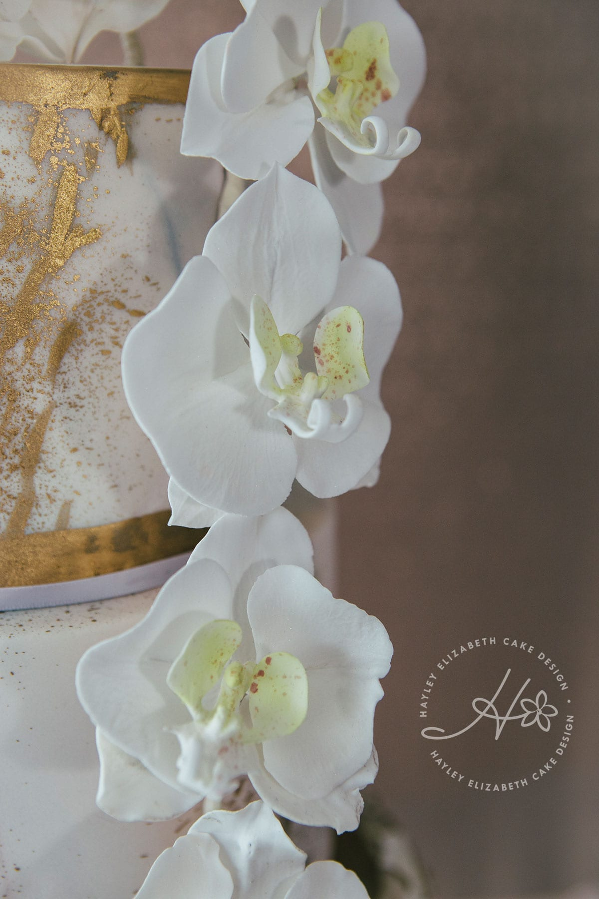 Luxury wedding cake with gold foil, marble effect icing, sugar flower orchids and ruffles. Elegant wedding cake, luxury cake design, wedding cake inspiration, beautiful wedding cakes, three tier wedding cake, white and gold wedding cake.