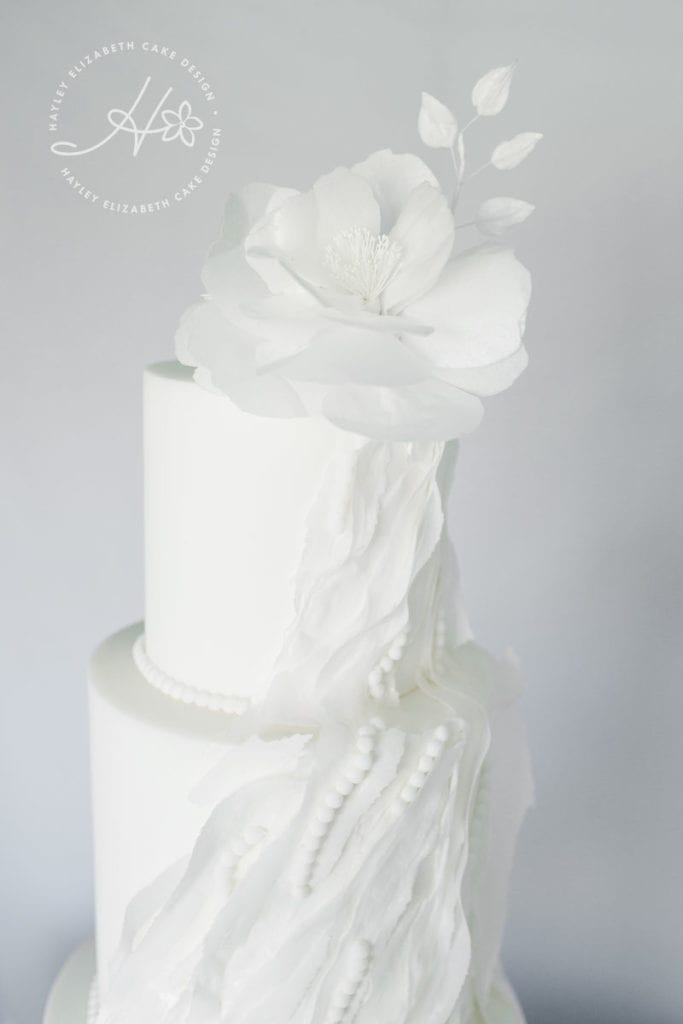 All white wedding cake, ruffle wedding cake, luxury wedding cake, elegant wedding cakes, fine art wedding cake, wedding cake inspiration, white shimmer wedding cake, winter wedding cakes, wedding cake ideas, white sugar flowers