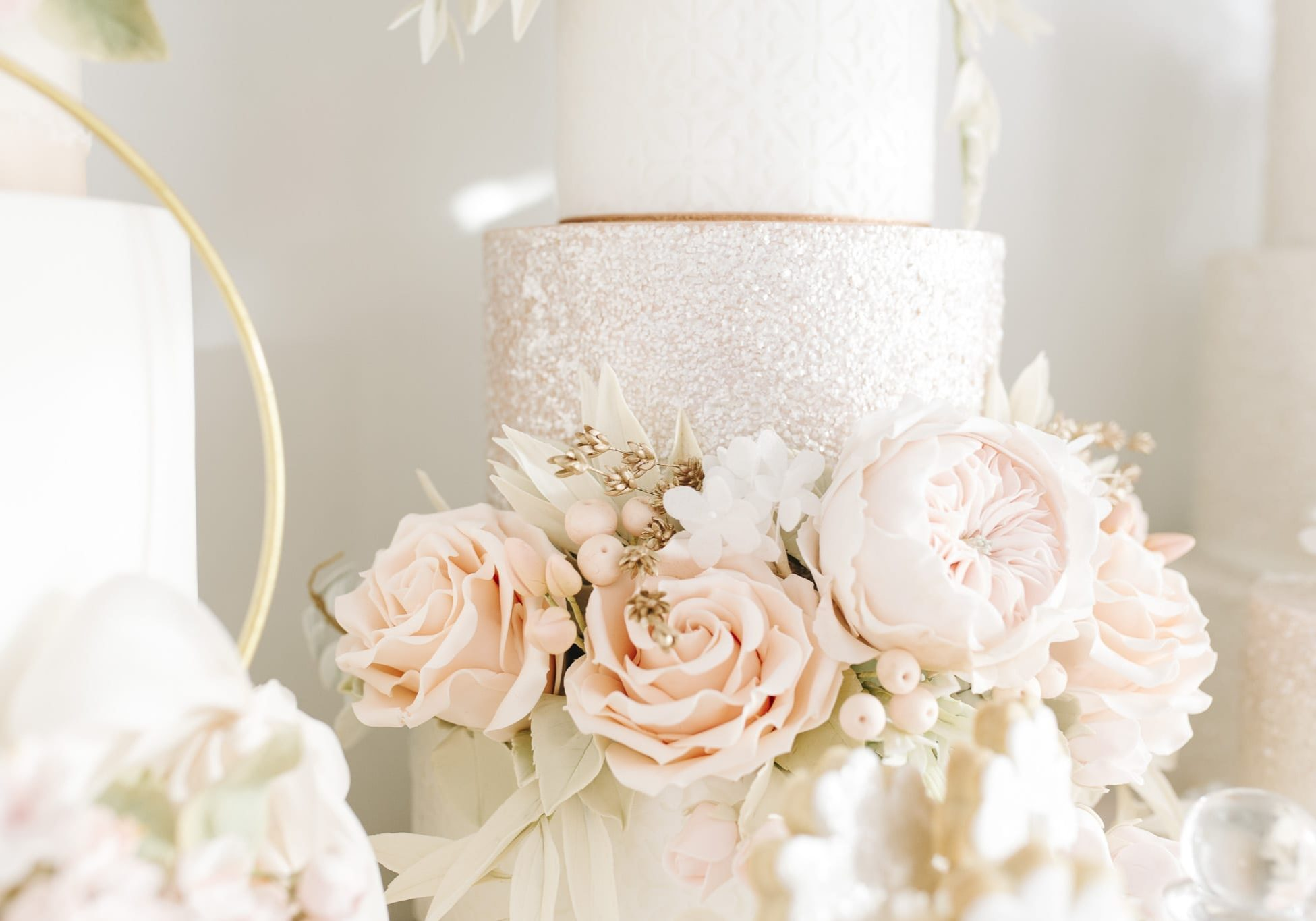 Luxury wedding cake from Hayley Elizabeth Cake Design, sugar flower peonies, foliage, sugar roses and rose gold shimmer. Fondant icing, textured wedding cake, dessert table, wedding cake inspiration